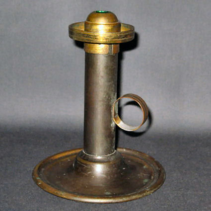 Spring loaded candlestick to maintain height of flame while burning. Brass top removes to add candle also has a shade holder